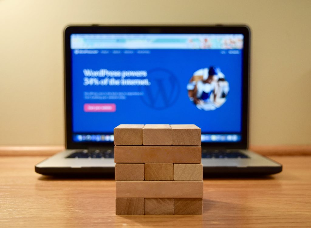 wooden building blocks in a stack pictured in front of a computer with a website builder open on screen