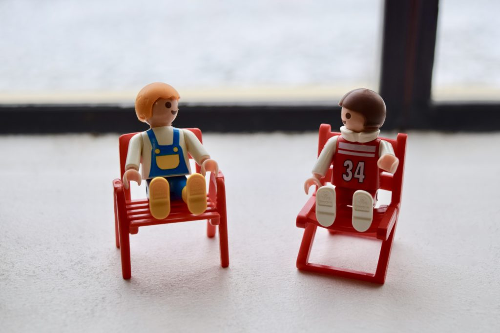 two small human toy figurines sitting on toy chairs facing one another as if in conversation