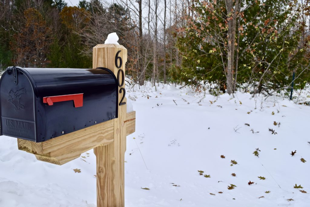 black mailbox on a wooden pole