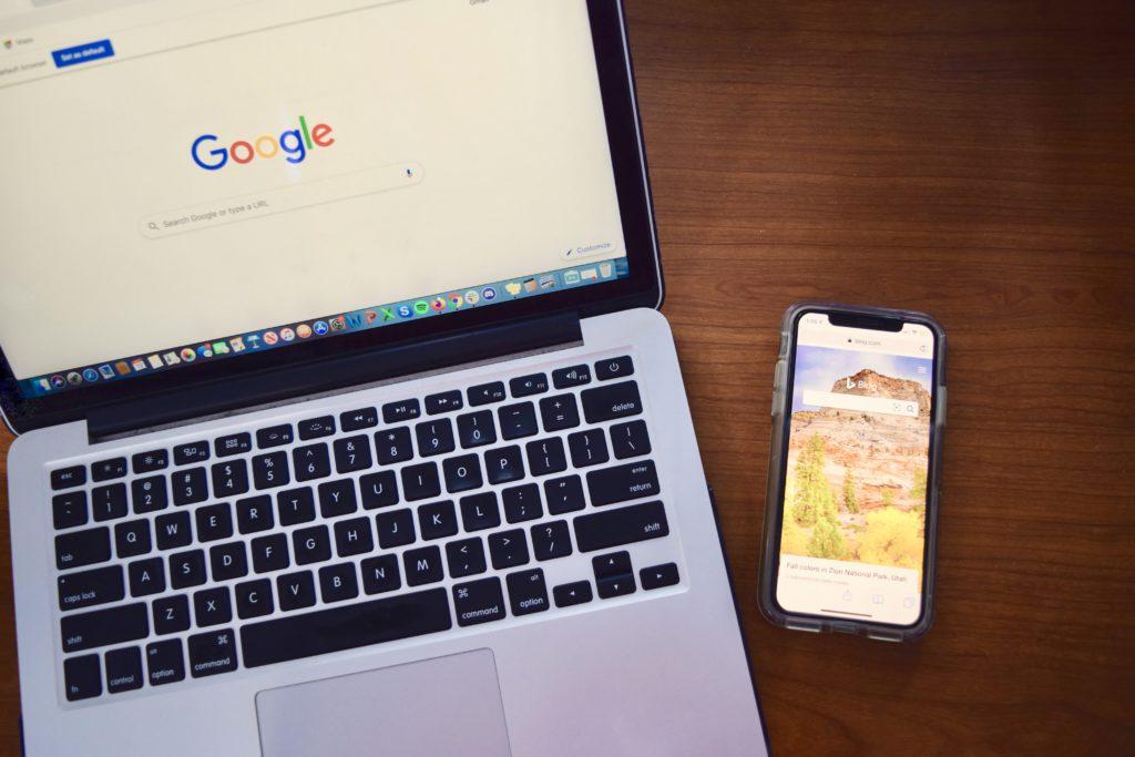 macbook laptop open to Google homepage alongside iPhone screen displaying Bing homepage