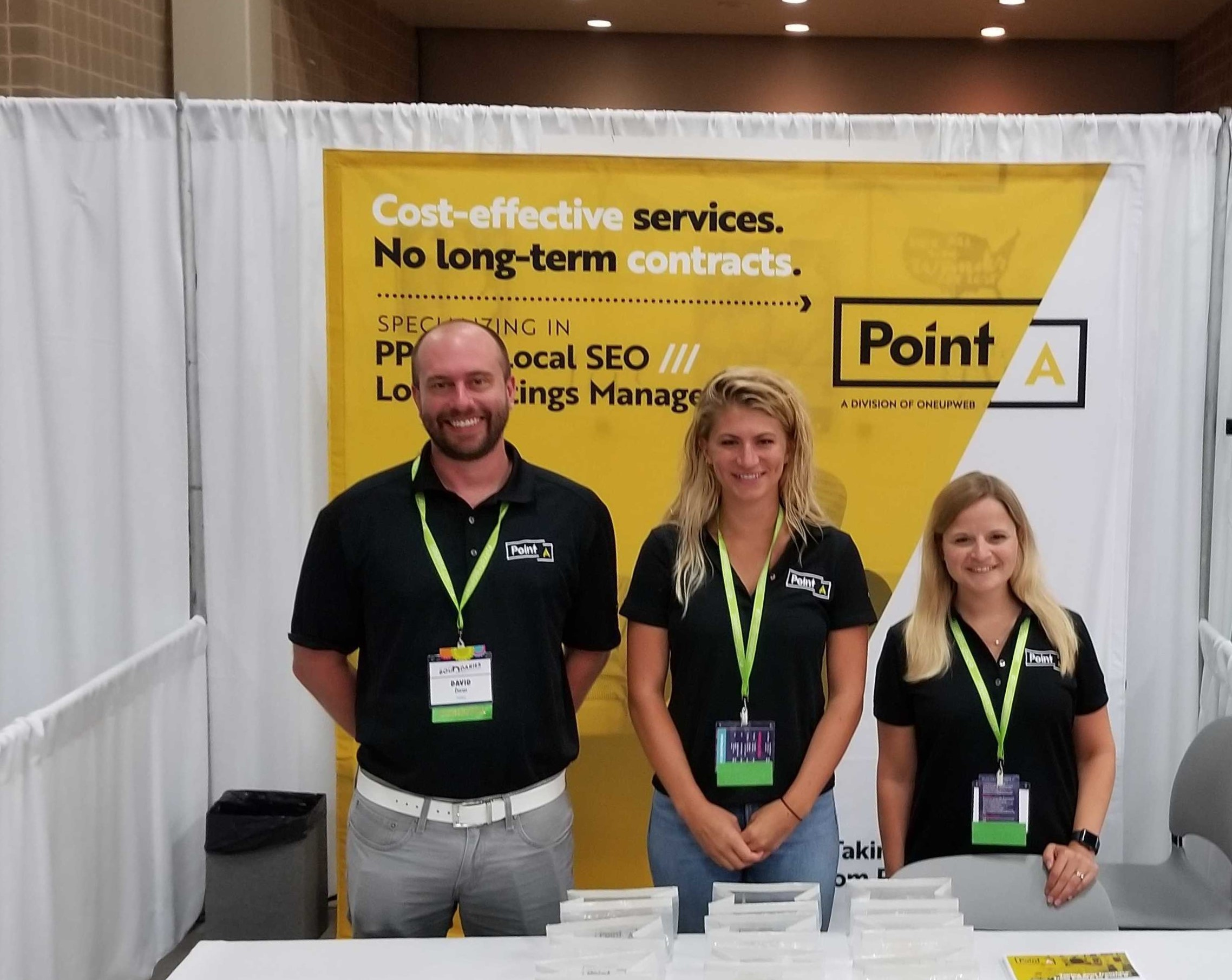 man standing next to two women at a PointA booth at a business conference