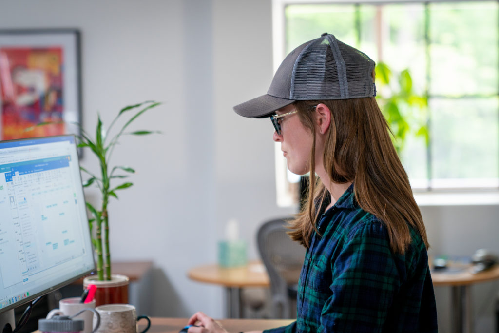 woman with long hair and baseball cap sitting in front of a desktop computer