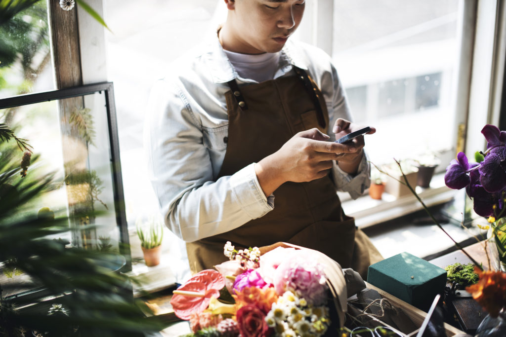 Man sitting using mobile at flower shop