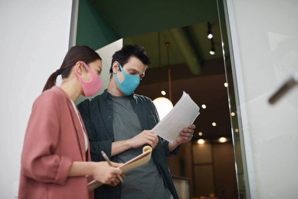 Two young business colleagues wearing protective masks they standing together and reading documents at office