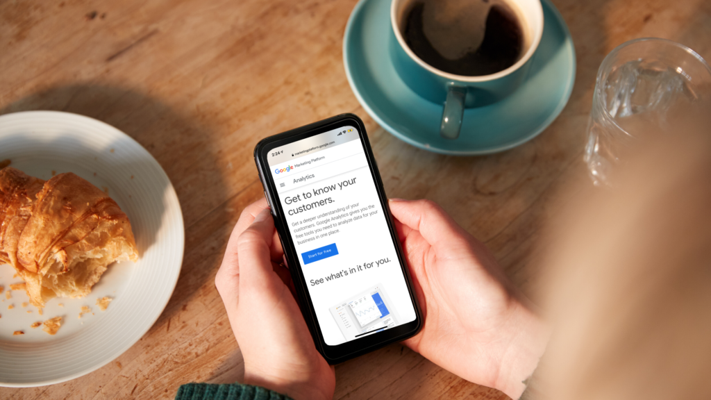 phone open to Google Analytics homepage held by two hands on a table with croissant and cup of coffee